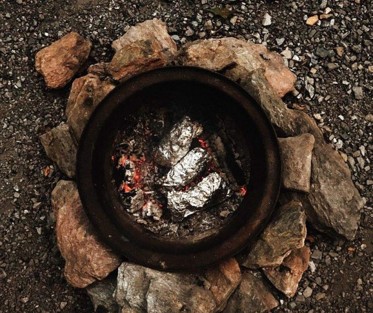 Camping recipes - fish in foil packets cooking over a campfire outside