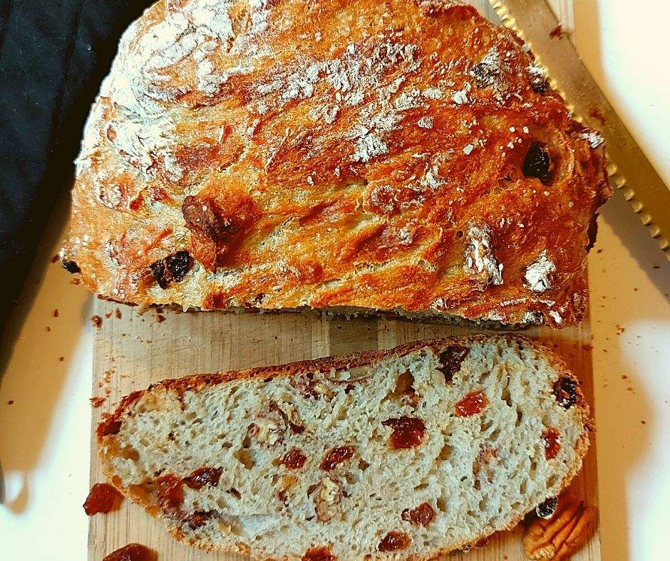 Cinnamon raisin bread with pecans on a cutting board with a bread knife