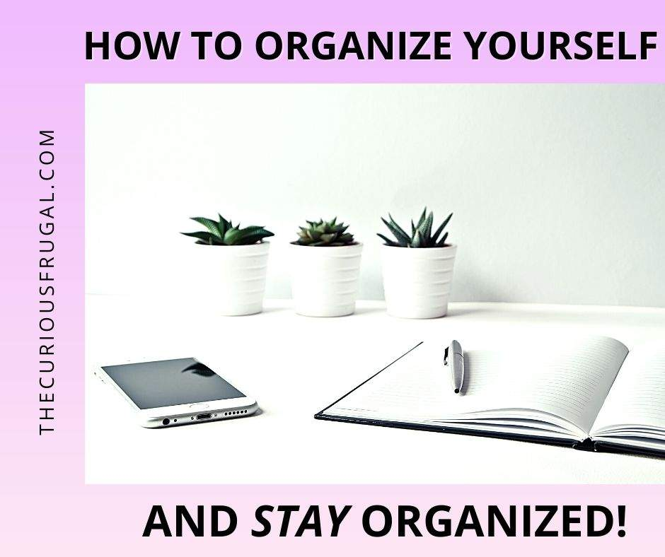 How to organize yourself and stay organized (lined notebook open with pen, smart phone and white plant pots on organized white table)